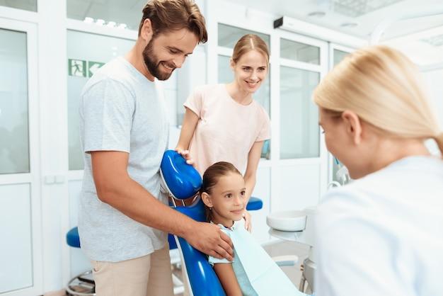 Los padres llevaron a su hija a la recepción con el dentista.