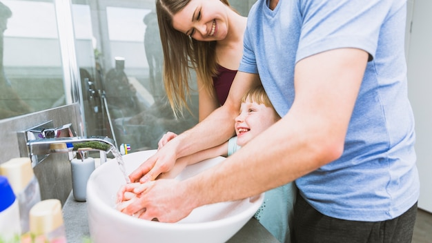 Los padres y la niña se lavan las manos