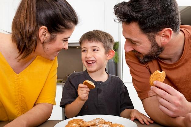 Los padres y el niño comiendo galletas de cerca
