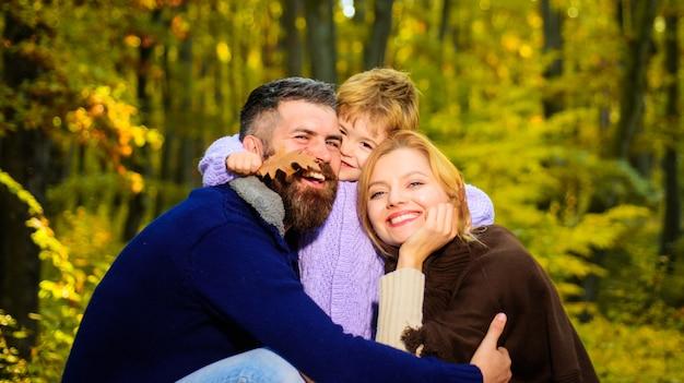 Los padres y el niño juntos en el parque día soleado de otoño la madre y el padre de familia feliz abrazan al pequeño hijo