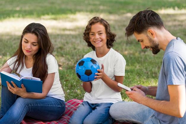 Los padres y el niño sonriente juntos afuera en el parque.
