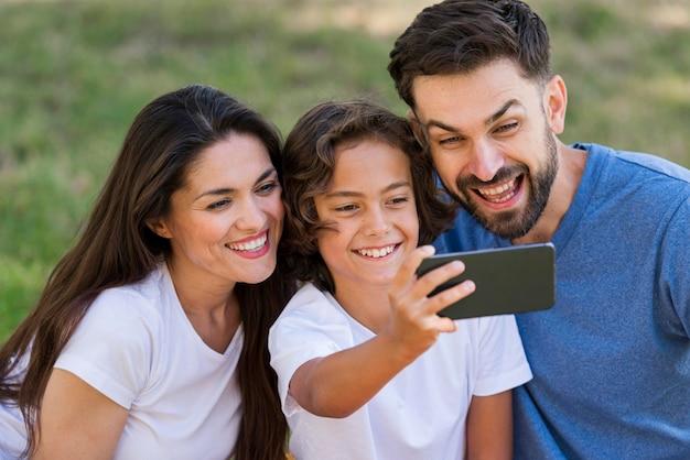 Los padres y el niño tomando selfie juntos al aire libre