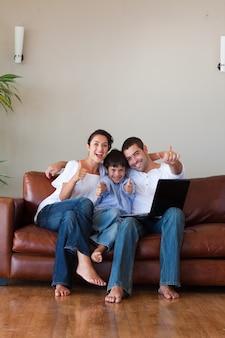 Padres y niños divirtiéndose con una computadora portátil y espacio de copia