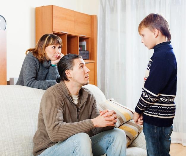 Padres ordinarios regañando hijo adolescente