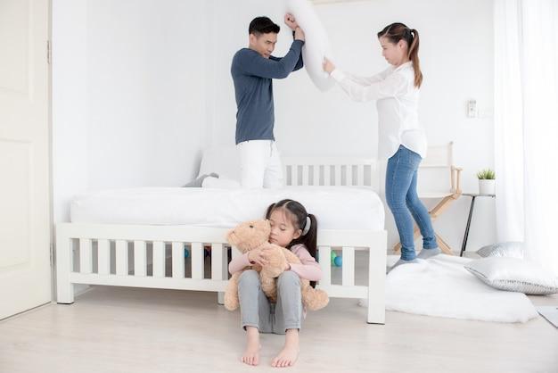 Los padres pelean entre ellos. la niña grita y se cubre las orejas con las manos. pareja peleando frente a niño.