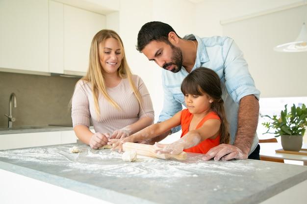 Los padres positivos viendo a su hija rodando masa en el escritorio de la cocina con harina desordenada. pareja joven y su chica horneando bollos o pasteles juntos. concepto de cocina familiar