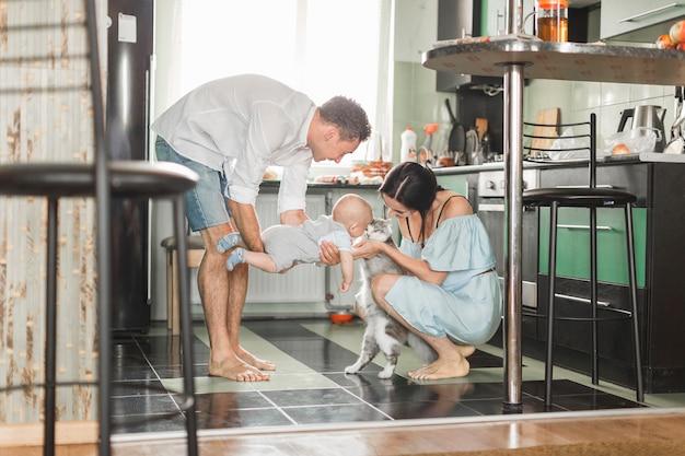 Padres que hacen amistad con su bebé y amigable gato en la cocina.