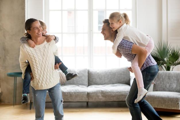 Padres que ríen dando a los niños a cuestas paseo jugando juntos en casa