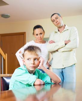Los padres regañan a un niño adolescente en casa
