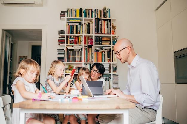 Padres sentados en casa mesa educación en el hogar con tres niñas