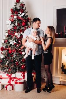 Padres sentados en el piso con el niño cerca del árbol de navidad.
