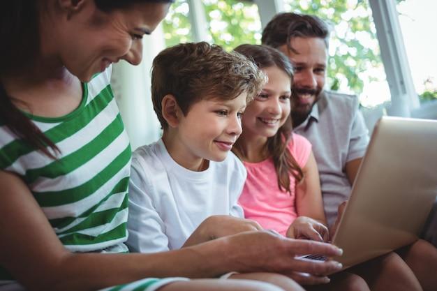 Padres sentados en el sofá con sus hijos y usando una computadora portátil en la sala de estar