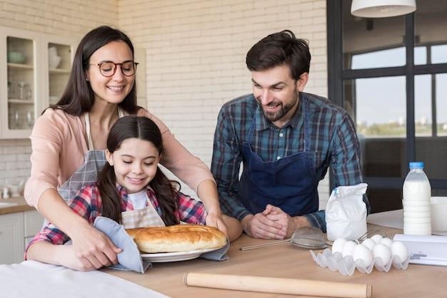 Padres sonrientes enseñando a niña a cocinar