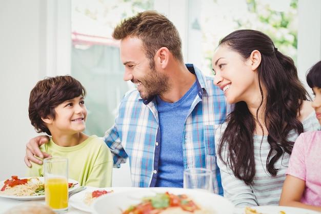 Padres sonrientes mirando a hijo en la mesa de comedor