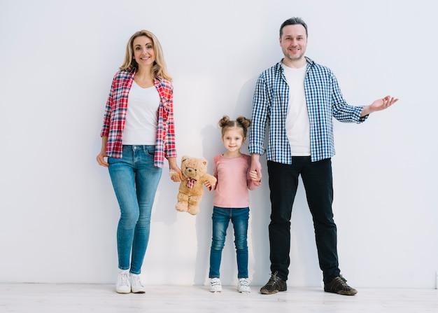 Padres sonrientes con su hija de pie contra la pared blanca