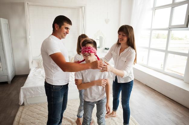 Padres sonrientes con sus hijos divirtiéndose en casa.