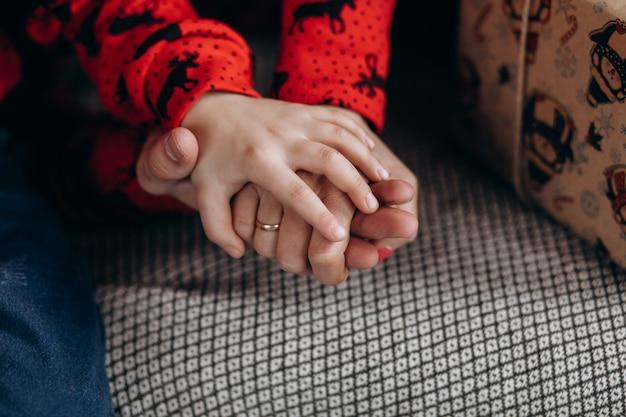 Los padres sostienen la mano tierna de su hijo.