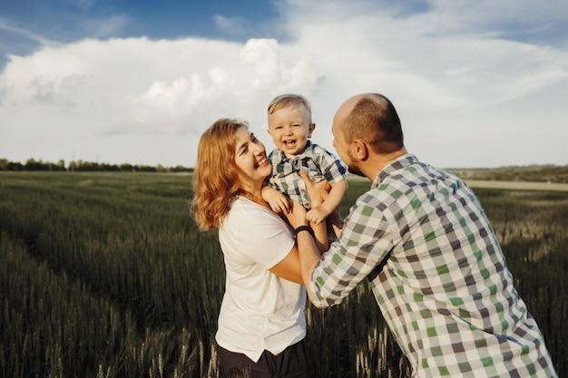 Los padres sostienen a su pequeño hijo y se divierten