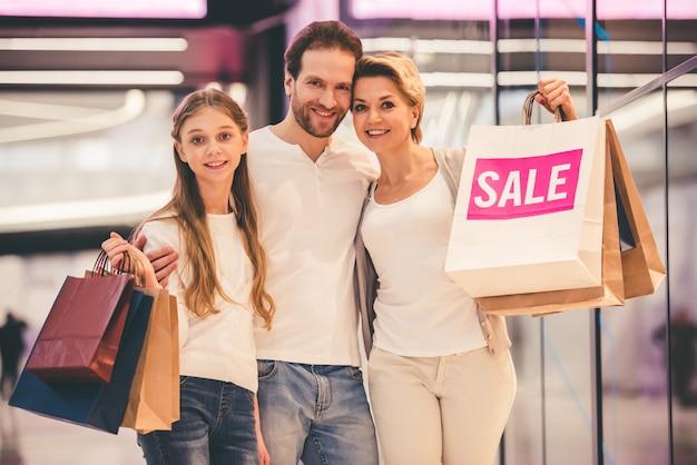 Los padres y su hija llevan bolsas en el centro comercial.