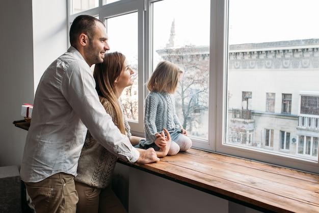 Los padres y su hija mirando en la ventana.