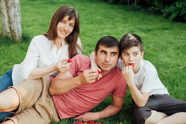Padres con su hijo sentado en el pasto y comiendo fresas.