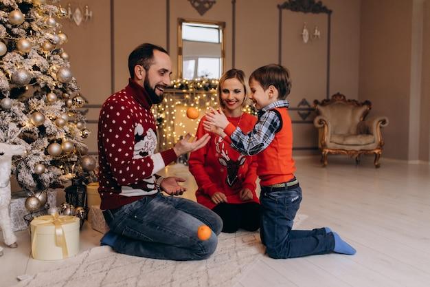 Los padres y su pequeño hijo en suéter rojo se divierten con naranjas sentadas ante un árbol de navidad