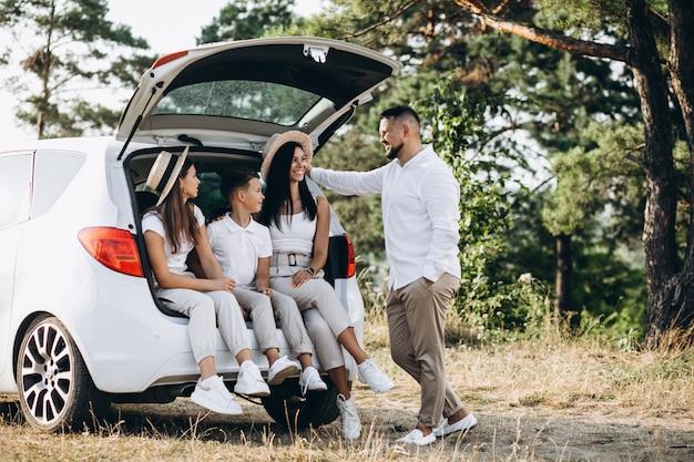 Padres con sus hijos en auto en el campo