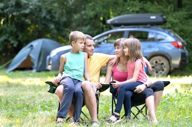 Los padres y sus hijos sentados juntos y hablando alegremente.