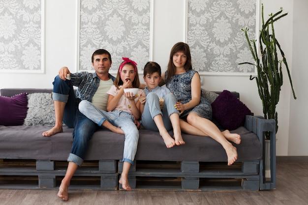 Padres y sus hijos sentados juntos en el sofá mirando a la cámara