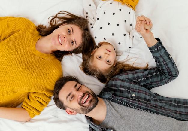 Padres de tiro medio y niño en la cama plana