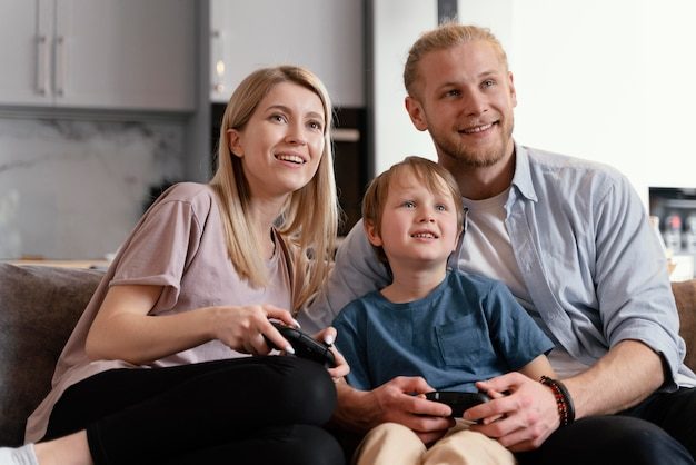 Padres de tiro medio y niños jugando juegos