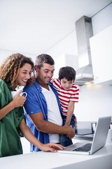 Padres usando laptop con hijo en la cocina