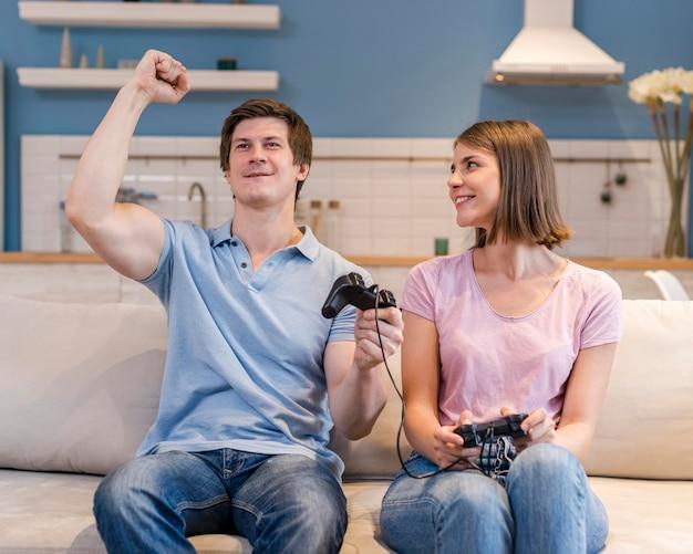 Padres de vista frontal jugando videojuegos juntos