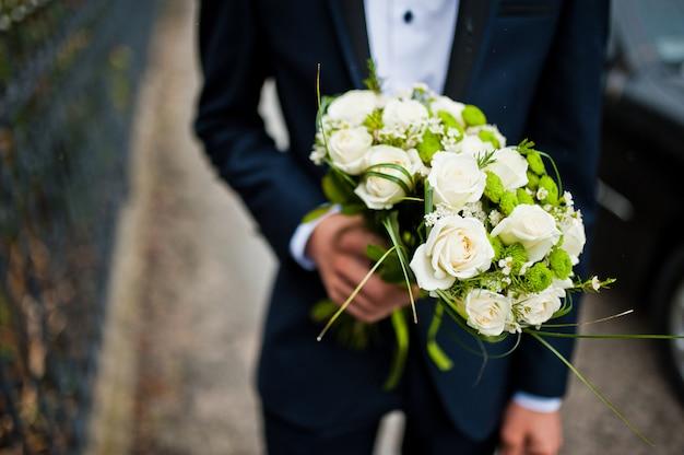 El padrino de boda tiene en la mano dos ramos de flores para damas de honor