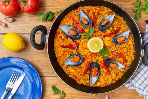Paella española en sartén sobre fondo de madera