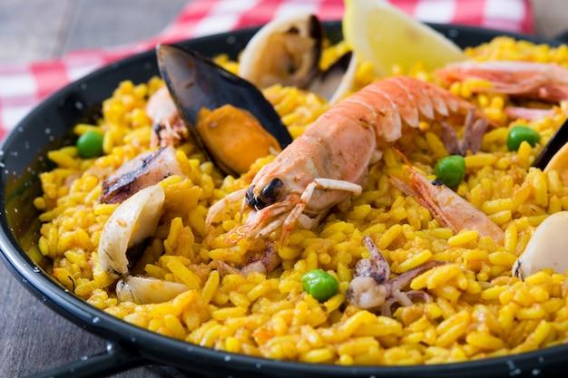 Paella española tradicional de mariscos en la mesa de madera de cerca