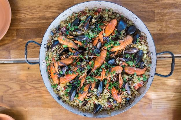 Paella de mariscos con mejillones y cangrejos en mesa de madera