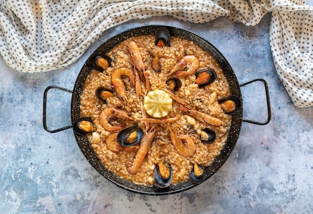 Paella de mariscos en mesa rústica
