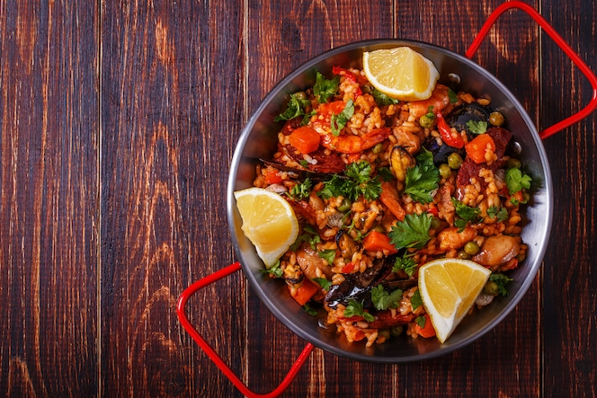 Paella de pollo, chorizo, marisco, verduras y azafrán servida en la sartén tradicional
