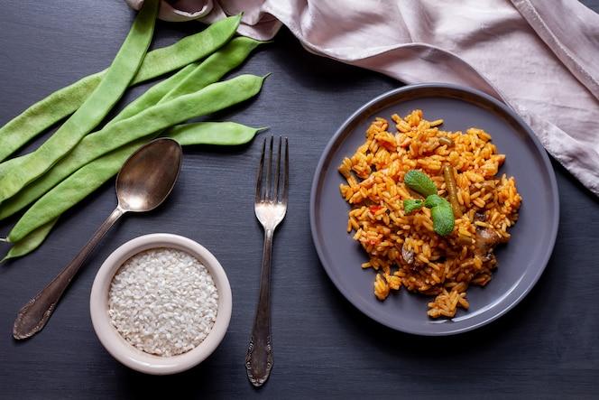 Paella de verduras y pollo en mesa negra, tazón de arroz, frijoles y cuchara y tenedor