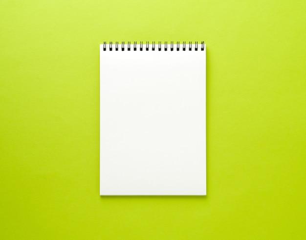 Página blanca de la libreta en blanco en el escritorio verde, fondo del color. vista superior, vacía para texto.