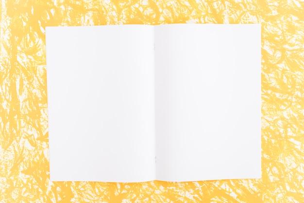 Página en blanco blanco sobre fondo amarillo con textura