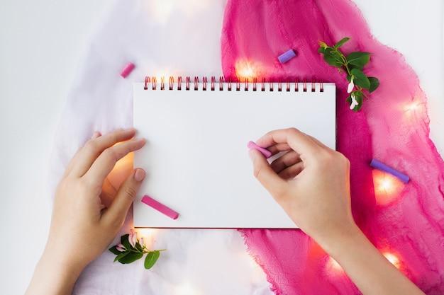 Página en blanco de cuaderno abierto y artículos de decoración en rosa y blanco