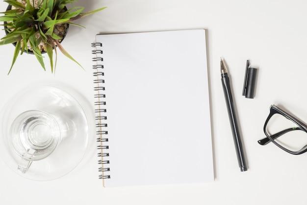 La página en blanco del cuaderno está encima de la mesa blanca del escritorio de oficina con las fuentes. vista superior, aplanada.