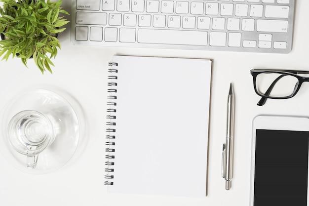La página en blanco del cuaderno está encima de la mesa blanca del escritorio de oficina.