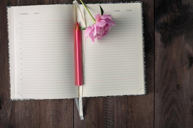 Página en blanco de cuaderno y lápiz, flor rosa en mesa de madera
