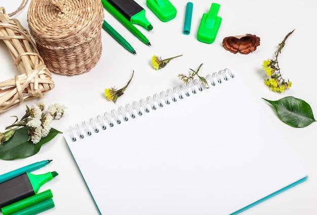 Página en blanco de la libreta espiral en mesa blanca. lápiz de crayón y lápiz plano. página de cuaderno de bocetos vacía en la vista superior de la mesa.