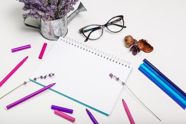 Página en blanco de la libreta espiral en mesa blanca. lápiz de crayón y pluma plana foto puesta. página de cuaderno de bocetos vacía en la vista superior de la mesa.