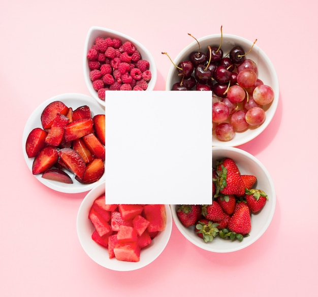 Página en blanco sobre las frambuesas; ciruelas sandía; fresas; guindas; uvas y fresas sobre fondo rosa