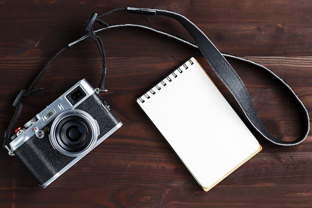 Página de bloc de notas en blanco y cámara moderna en estilo clásico en mesa de madera marrón oscuro